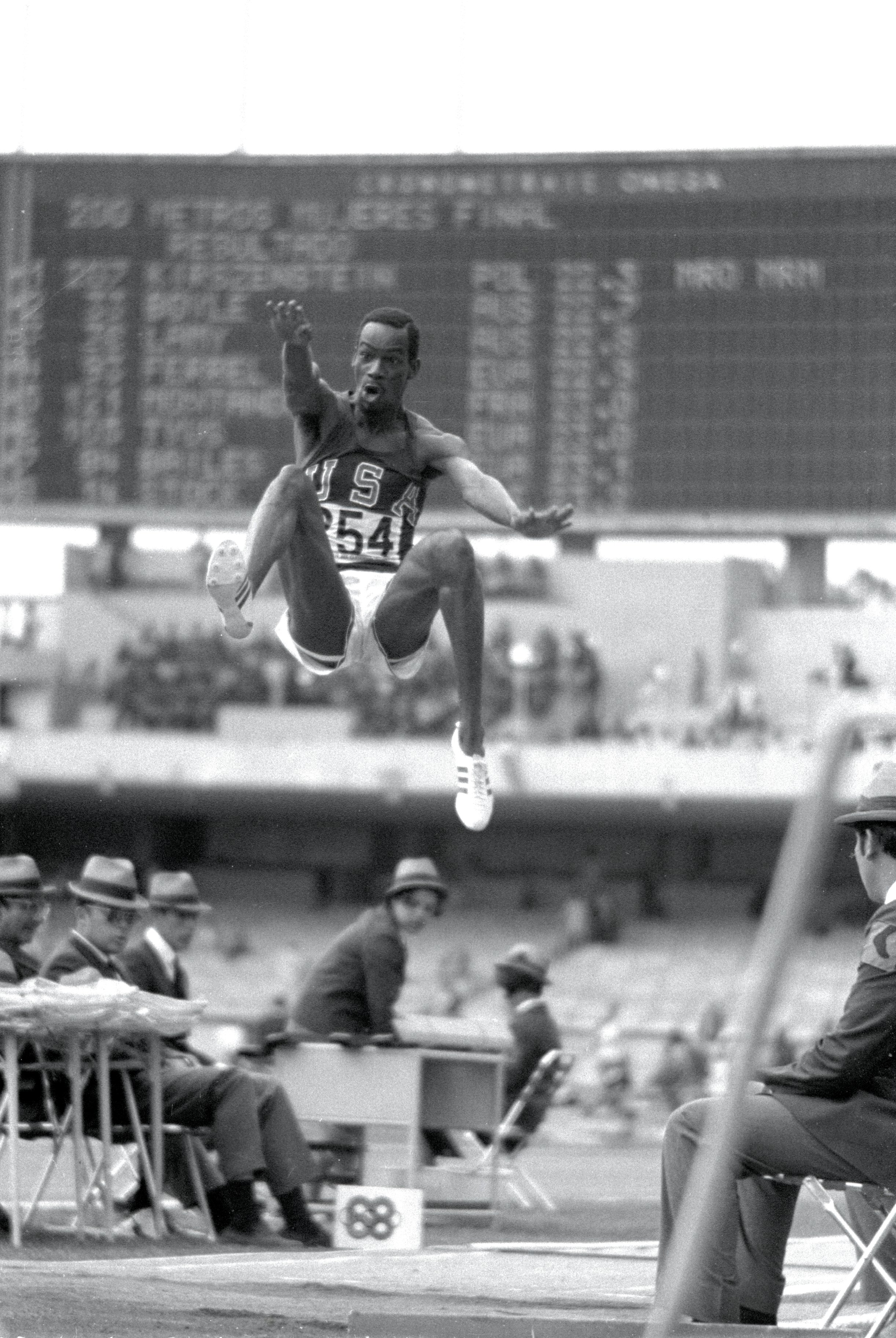 18 Oct 1968: Bob Beamon #254 of the USA breaking the Long Jump World Record during the 1968 Olympic Games in Mexico City, Mexico. Beamon long jumped 8.9 m (29 ft 2 1/2 in), winning the gold medal and setting a new world record. It is the first jump over 28 ft. The most famous long jump ever achieved: Bob Beamon of the United States takes off for a place in sporting history as he leaps 8.90 metres at the Mexico City Games of 1968. While the middle distance runners from the low level countries floundered in the thin air of Mexico City, those in the explosive events reached new peaks, none higher than Beamon, who added 58 centimetres to the world record with a jump aided by a wind of 2 metres per second the very limit of wind assistance. In Imperial measure terms it looked even more impressive since he missed out 28 feet, taking the record to 29 ft 2 ins. Yet Beamon never again managed a jump of 27 feet. It was twelve years before anyone else reached 28 feet (8.53 metres) and the record stood until 1991 when Mike Powell of the US leapt 8.95 metres in Tokyo to win the world title. His jump was at sea level and wind assistance of 0.3mps. Mandatory Credit: Tony Duffy /Allsport
